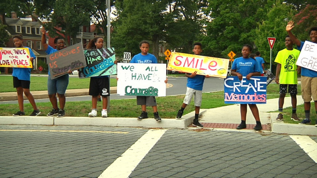 Kids flash peaceful message signs near Lee monument