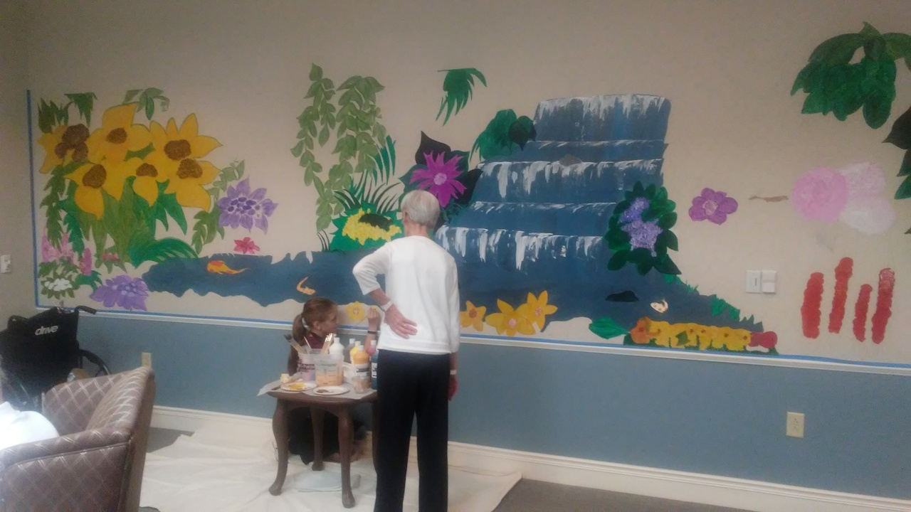 Memory care residents and children paint wall mural